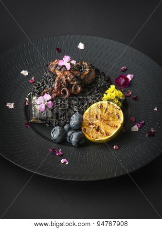 Risotto With Octopus And Blueberries On A Black Plate
