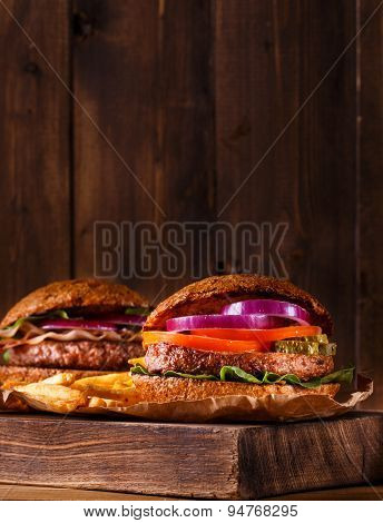 Two burgers close up on a cutting board.