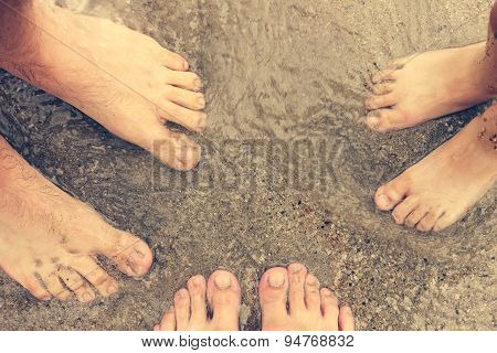 Feet of three people standing in the sea. Family resting on the beach and swimming in the sea.