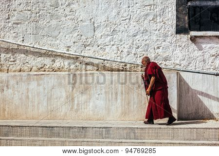 SPITUK, INDIA - SEPTEMBER 15, 2012: Old buddhist monk walking along the wall of Spituk gompa, Ladakh, India