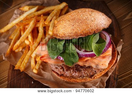 Burger and french fries on wooden background.