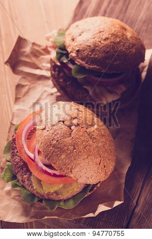 Burger on wooden background.