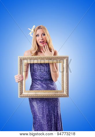 Woman with picture frame against gradient