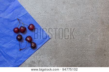 Cherry On Blue Paper And Gray Background From Stone