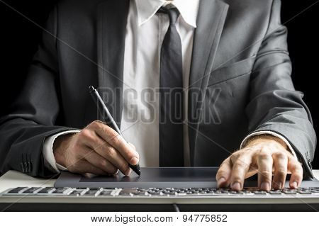 Front View Of Male Graphic Designer  Sitting At His Office Desk Working With Stylus Pen