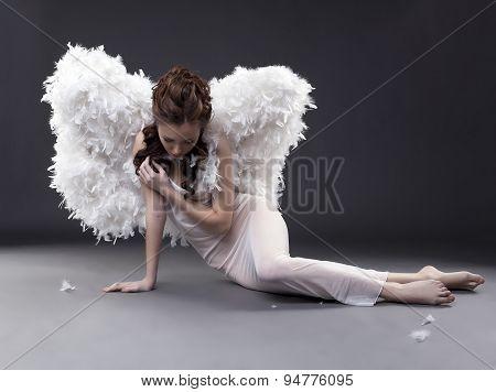 Fascinating girl in angel costume posing at camera