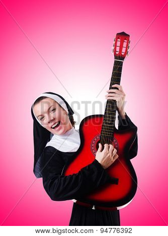 Nun playing guitar against the gradient