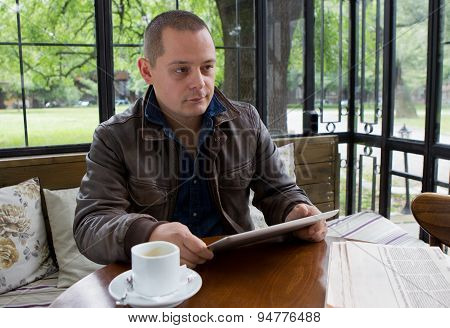 A Happy Man Reading An Ebook In A Coffee Shop