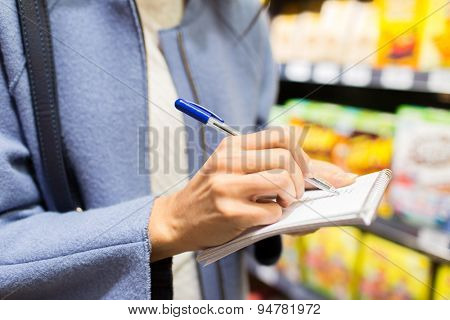 sale, shopping, consumerism and people concept - close up of young woman with pen taking notes to notebook in market