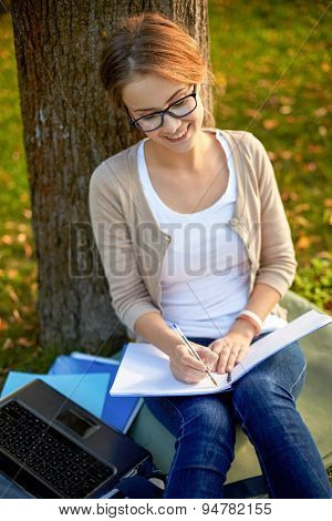 summer, education, learning and teenage concept - happy student girl with laptop computer writing to notebook at campus