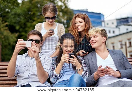 summer, technology, education and teenage concept - group of happy students or teenagers with smarphones taking selfie and texting messages at campus