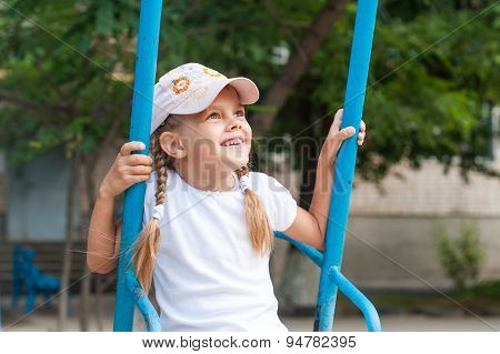 Happy Girl Riding On A Swing