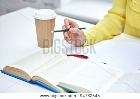 people and education concept - close up of female hands with books and coffee