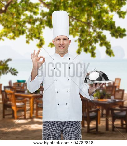 cooking, profession, gesture and people concept - happy male chef cook holding cloche and showing ok sign over restaurant lounge on beach