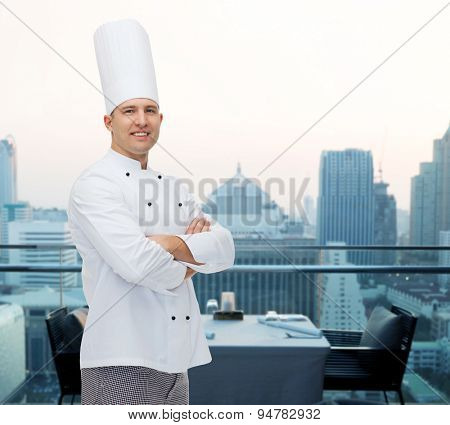 cooking, profession and people concept - happy male chef cook with crossed hands over city restaurant lounge background