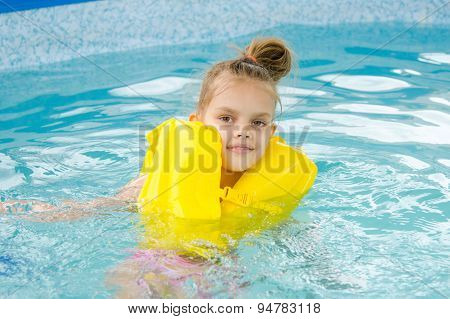 Girl Swimming In The Pool In The Lifejacket