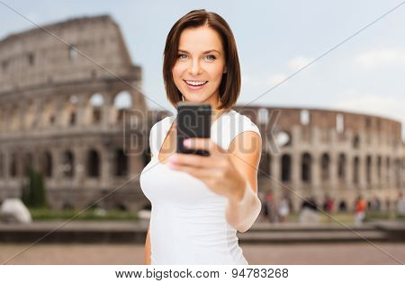 people, technology, tourism and travel concept - young woman taking selfie with smartphone over coliseum background