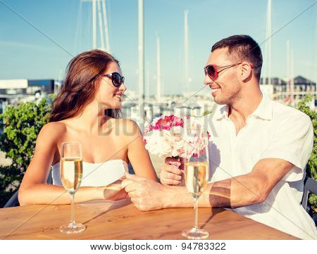 love, dating, happiness and people concept - smiling couple wearing sunglasses with bunch of flowers and champagne glasses looking to each other at cafe
