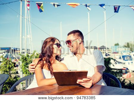 love, dating, people and food concept - smiling couple wearing sunglasses holding menu and looking to each other at cafe