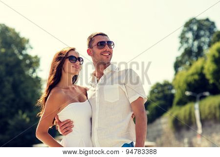 love, travel, tourism, people and friendship concept - smiling couple wearing sunglasses hugging and pointing finger in park