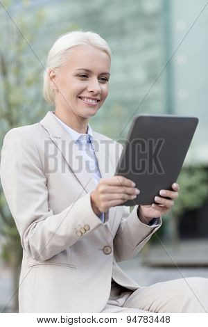 business, education, technology and people concept - smiling businesswoman working with tablet pc computer on city street
