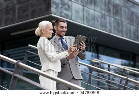 business, partnership, technology and people concept - smiling businessman and businesswoman working with tablet pc computer on city street