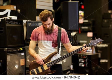 music, sale, people, musical instruments and entertainment concept - male musician or customer with beard playing bass guitar guitar at music store