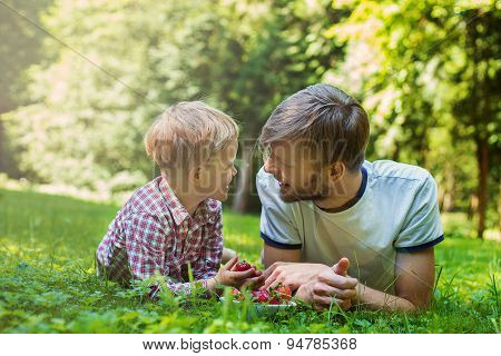 Summer photo happy father and son together lying on green grass. Life moment family