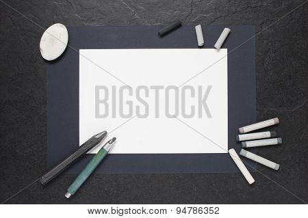 Sheet Of Paper And Painting Supplies On The Table