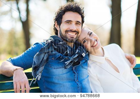 Young couple in love sitting together on the bench in the park