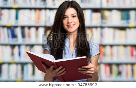 Beautiful young student in a library