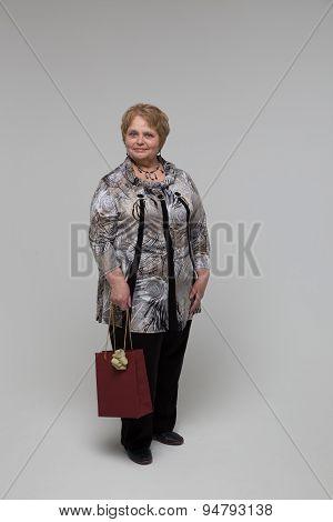 Portrait of an elderly happy woman on a grey background