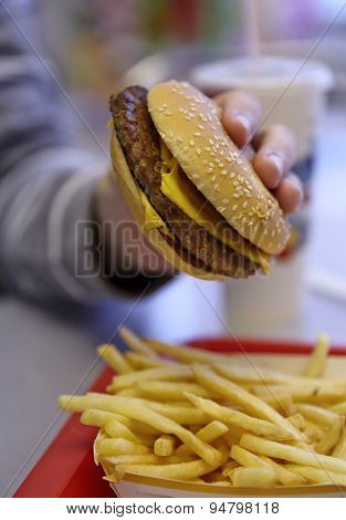 Hand holds big hamburger