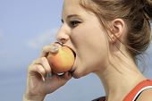 stock photo of 13 year old  - A Girl Eat Peach with the sky on the back - JPG