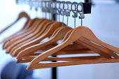 stock photo of clothes hanger  - empty clothes hangers lined up in a room - JPG