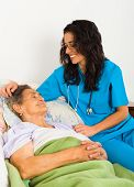 stock photo of nurse  - Kind nurse easing elderly lady - JPG
