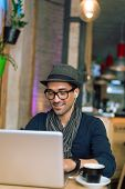 stock photo of internet-cafe  - Fashionable and stylish young man relaxing with coffee music and internet browsing at the cafe bar. Selective focus. ** Note: Visible grain at 100%, best at smaller sizes - JPG