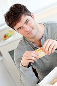 Attractive Young Man Eating Bread Sitting In His Kitchen