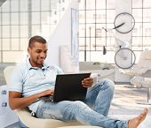 foto of afro  - Relaxed casual afro american man browsing online with laptop computer at bright loft apartment - JPG