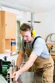 pic of workplace safety  - Carpenter working on an electric buzz saw cutting some boards - JPG