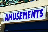 stock photo of amusement  - Amusements sign over the entrance of a holiday seaside amusement park - JPG