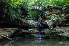 image of ravines  - Ancient stone footbridge crosses over a ravine with a waterfall flowing into a natural lagoon - JPG