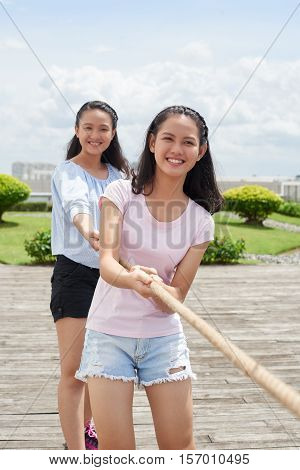Asian young sisters playing tug of war in one team