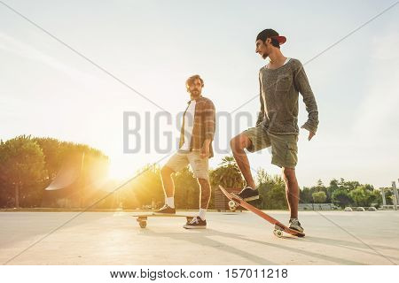 Young people training with longboard with back sun light- Skaters friends outdoor in urban city with skateboards -Extreme sport and friendship concept - Focus on right man's feet - Warm filter
