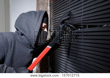 Thief trying to open window