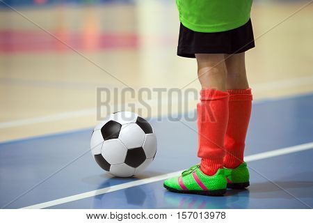 Football futsal training for children. Indoor soccer young player with a soccer ball in a sports hall. Player in yellow and red uniform. Sport background.