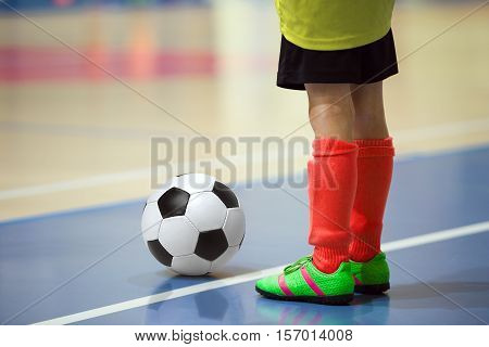 Football futbal training for children. Indoor soccer young player with a soccer ball in a sports hall. Player in yellow and red uniform. Sport background.