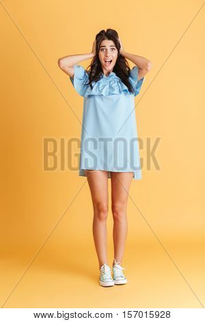 Full length portrait of a scared young brunette woman standing with mouth opened over orange background