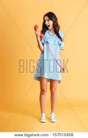 Full length portrait of a crazy raged young woman shouting in red telephone receiver isolated on a orange background
