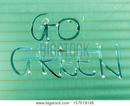 picture of a Handwritten text Go Green on a Frosted Glass Texture.Green effect added